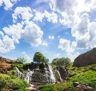 Mountain waterfall with blue cloudy sky Stock Photos
