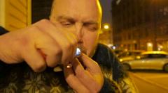 Man smokes weed. Rastaman on a night street. 4K UHD Stock Footage