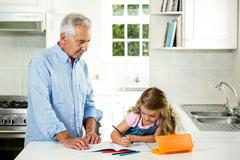 Girl studying at table with granddad Stock Photos
