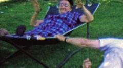 1962: Grandpa shakes hammock annoys excites Grandma. - stock footage