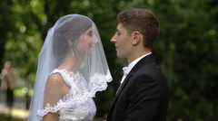 The groom lifts the veil from the bride's face and kisses her Stock Footage