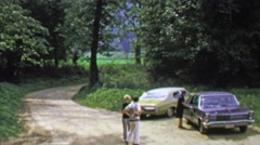 1974: Countryside parking lot classic cars gravel road spring green. Stock Footage