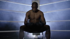 4K Aggressive fighter sits in corner of ring, psyching himself up for the fight. - stock footage