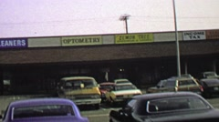 1974: Strip mall parking lot business storefront signs and logos. - stock footage