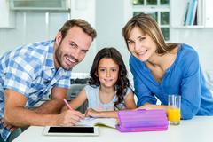 Happy father and mother assisting daughter in homework at home - stock photo