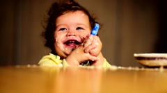 Little cute baby in the kitchen smeared face and laughs Stock Footage