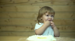 Stock Video Footage of beautiful baby over wooden table licks fingers and smiling happily