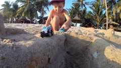 Boy Plays on the Beach in the Sand With Toys Stock Footage