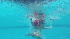 A Little Boy Dives Under the Water in the Pool Stock Footage