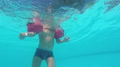 a Little Boy Floats Under Water in the Pool - stock footage