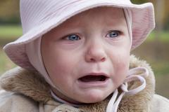 Little girl with pink cap crying - stock photo