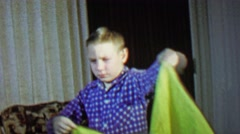 1967: Boy performs magic trick makes orange appear from nothing. - stock footage