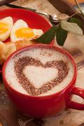 Coffee in red mug with hearth shape cocoa dust for valentines day Stock Photos