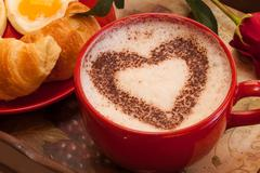 Coffee in red mug with hearth shape cocoa dust for valentines day - stock photo