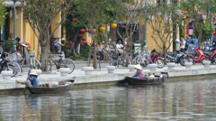 Boats at the thu bon river and tourists in the Old town of Hoi An Vietnam Stock Footage