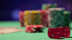 Rack focus shot of pile of poker chips and dice on table, casino background Stock Footage