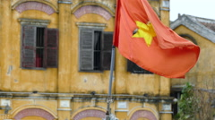 Vietnamese flag with old town buildings at the background Stock Footage
