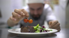 Chef is finishing meal teasty beef steak with salad for guest of restaurant Stock Footage
