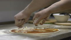 Chef putting cheese topping on his pizza base. Slow motion Stock Footage