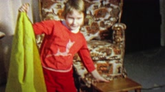 1967: Girl magician practice trick disappearing behind towel. - stock footage