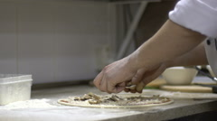 Chef putting mushrooms topping on his pizza base. Slow motion Stock Footage
