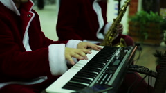 Musical band in Santa Claus suits playing merry melody to create Xmas atmosphere Stock Footage