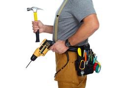 Builder handyman with drill and hammer. Stock Photos