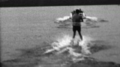 1962: Waterski man pulled behind speedboat dark mysterious lake. - stock footage