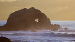 Rock with a heart shaped outline in the ocean. The Seal Rocks at sunset. Stock Footage