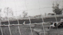 1939: Race track cars go kart racing behind thin wire safety fence. Stock Footage