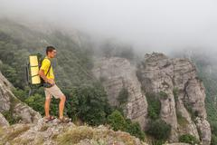 Hiker with backpacker in the foggy mountains Stock Photos