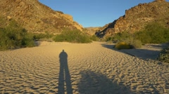 Long shadow of a man hiking in a desert wash Stock Footage