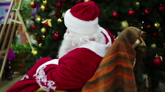 Happy Santa Claus waving hand in rocker chair to welcome shopping mall visitors Stock Footage