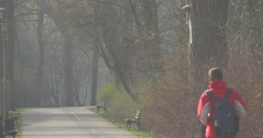 Tall Man Goes on Asphalted Road Into Central Park of a City of Opole Stock Footage