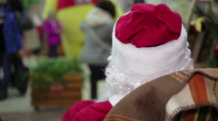 Back view of Santa Claus looking at busy passers-by in crowded trade center Stock Footage