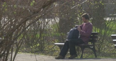 Tourist Sits on Old Wooden Bench in Central Park of a City of Opole (Poland) Stock Footage