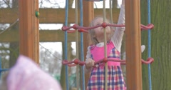 Little Girl Slowly Climbs Upwards on Rope Ladder Stock Footage