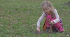 Girl Digs a Hole in Ground by Means of a Stick Stock Footage