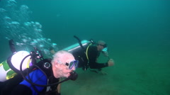Buddy team of scuba divers swimming on inshore wreck on deep sand in Australia, Stock Footage