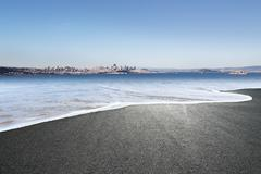 Asphalt road covered by seawater in summer day in new zealand Stock Photos