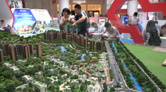 Chinese couple looks at miniature homes and apartment blocks Stock Footage