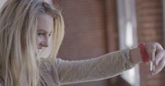 CU attractive blonde girl taking selfies in urban hallway 4K Stock Footage
