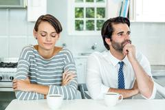 Unhappy couple sitting at table in kitchen - stock photo