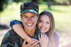Happy soldier reunited with his partner in the park - stock photo