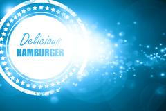 Blue stamp on a glittering background: Delicious hamburger sign - stock illustration