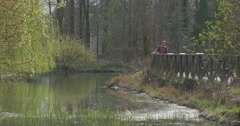 Man on Wooden Bridge Takes Tablet From Backpack Small River With Stony Bank Stock Footage