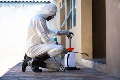 Side view of a man doing pest control - stock photo