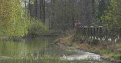 Man With Tablet on Bridge Over River in Spring Park Ripple Sun Reflection in Stock Footage