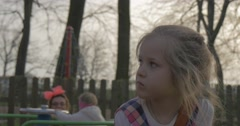The Little Girl Sits on a Wooden Bench Stock Footage