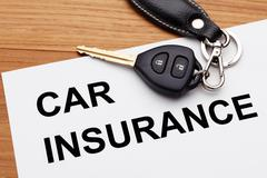 Car insurance concept with car key on wood table - stock photo